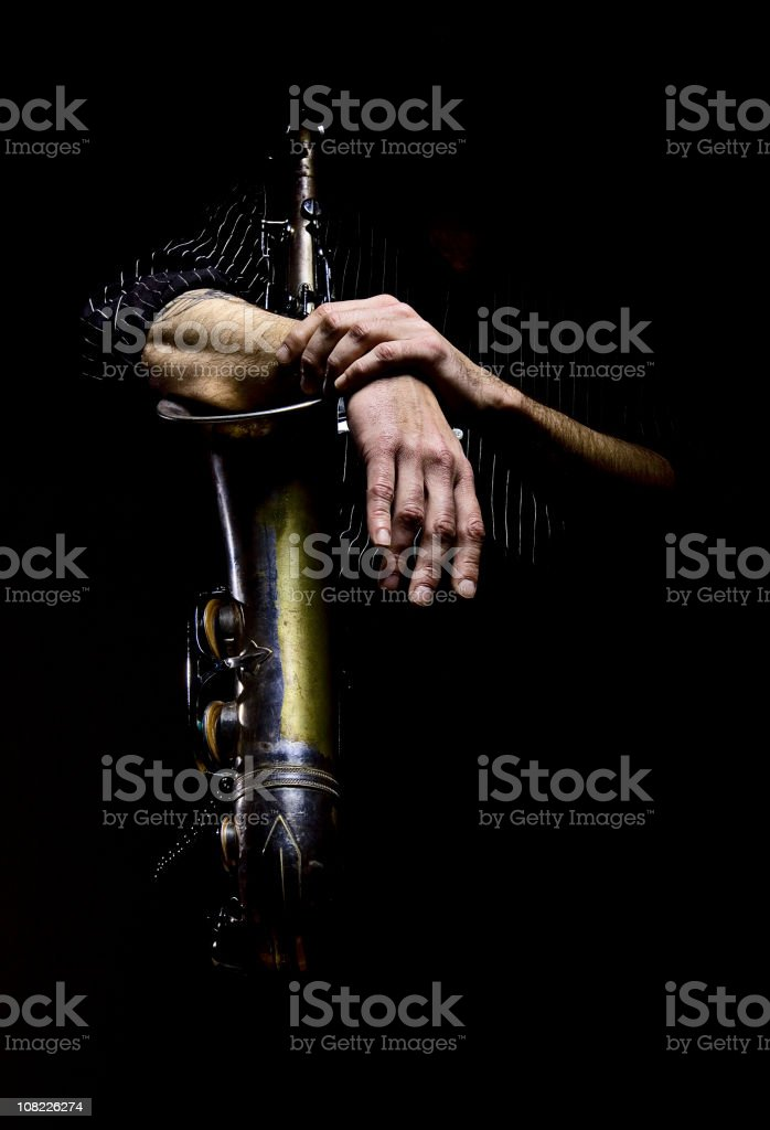 Man's Arms Wrapped Around Saxophone, Low Key stock photo