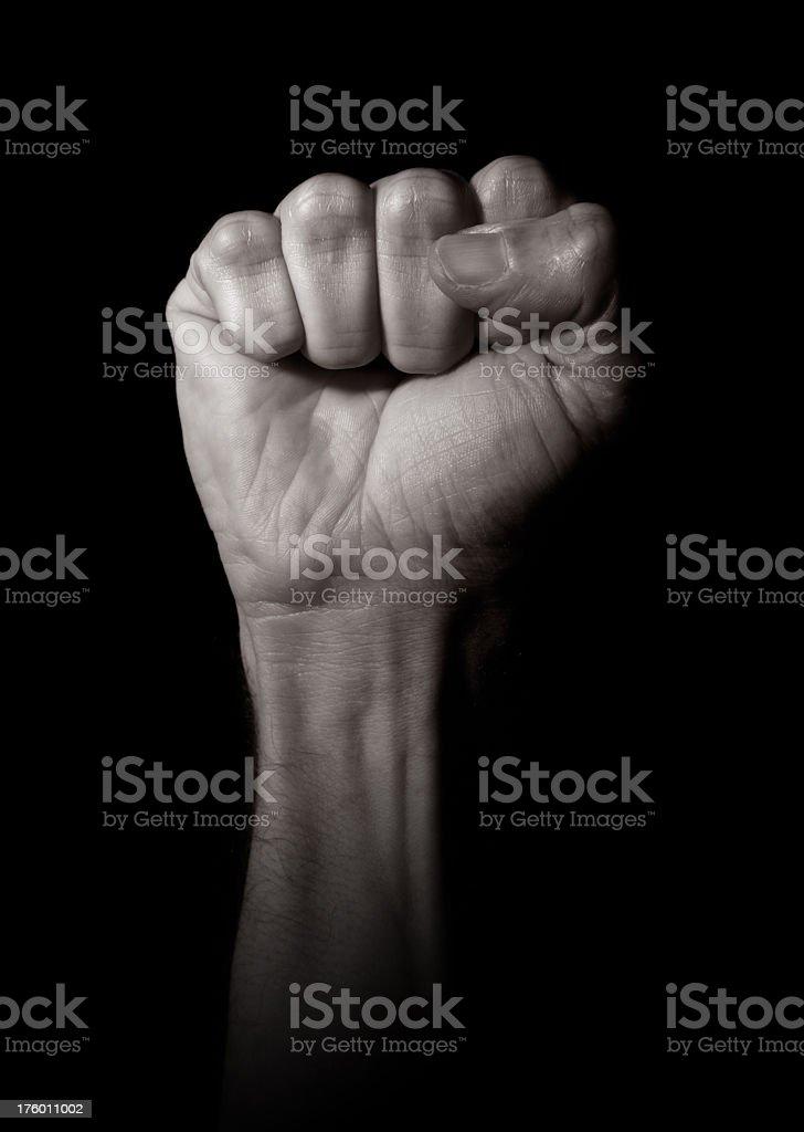 A mans clenched fist on a black background royalty-free stock photo