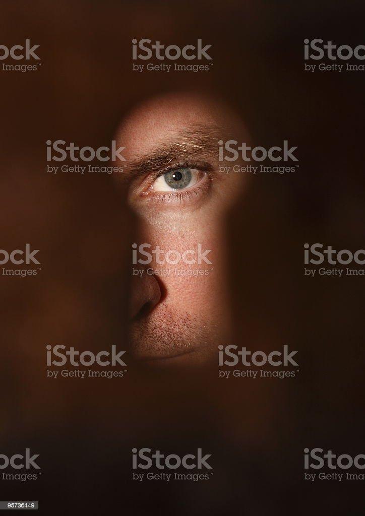 Man's eye illuminated by a bright keyhole royalty-free stock photo