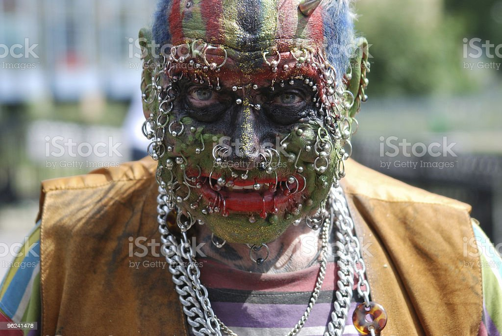 Man's face covered in piercings and face paint stock photo