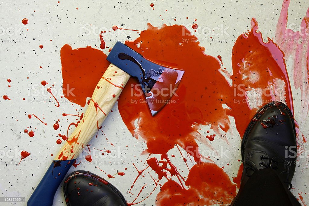 Man's Feet and Axe in Puddle of Blood stock photo