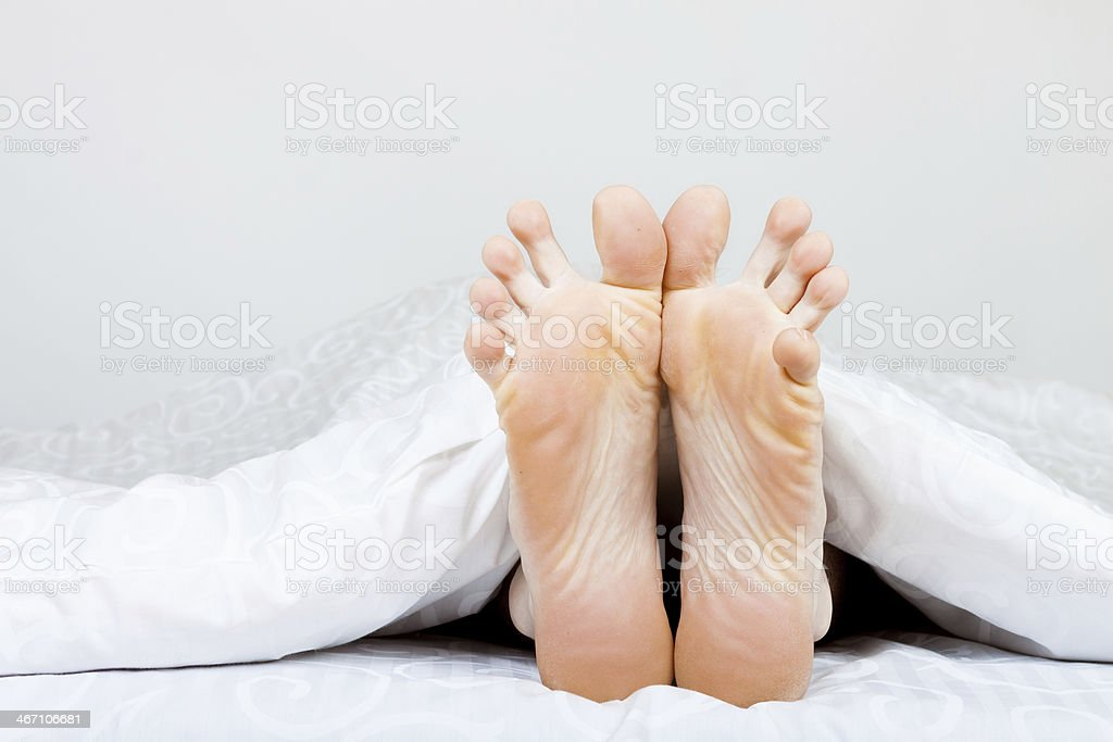 man's feet in bed royalty-free stock photo
