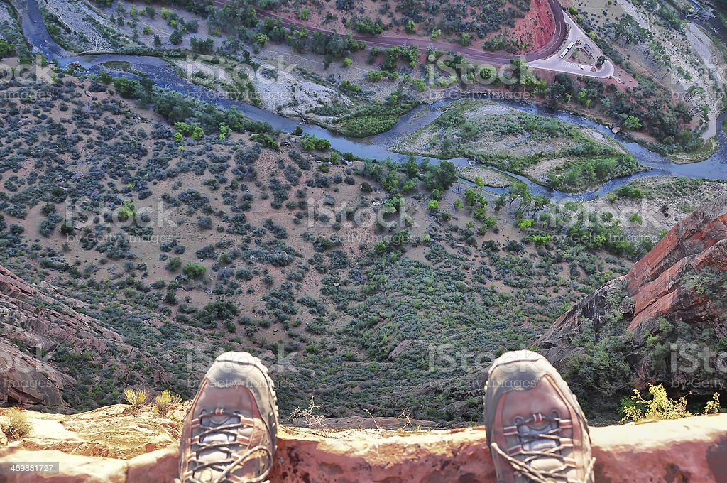 Man's feet on the edge of rock cliff royalty-free stock photo