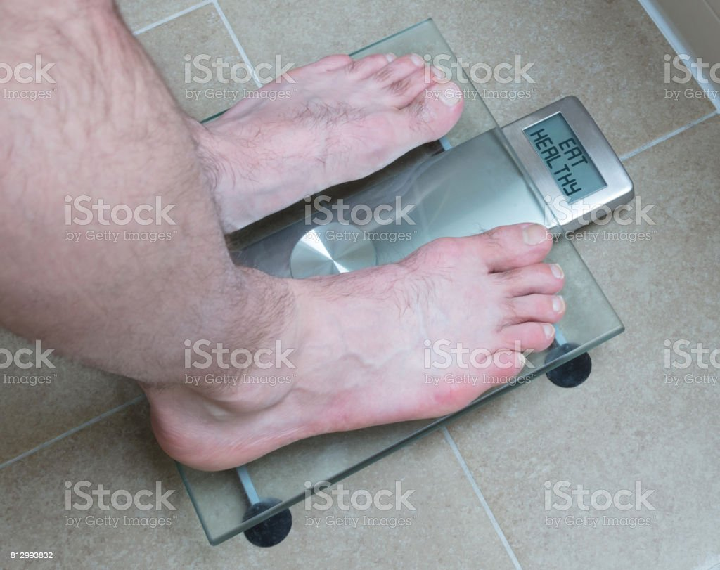 Man's feet on weight scale - Eat healthy stock photo