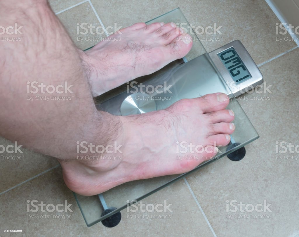 Man's feet on weight scale - OMG stock photo