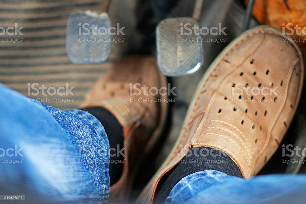 Mans feet pushing on the accelerator of automobile stock photo