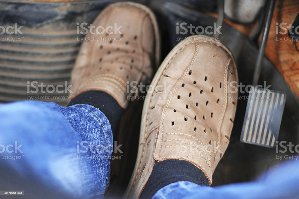 Mans feet pushing on the accelerator stock photo