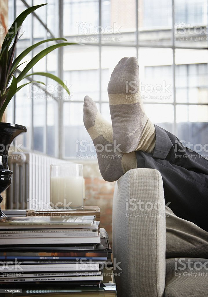 Man's feet up on arm of couch in modern home stock photo