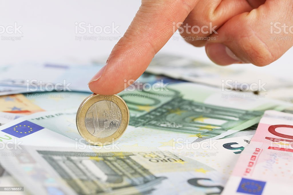 Man's finger holding one euro coin on euro banknotes stock photo