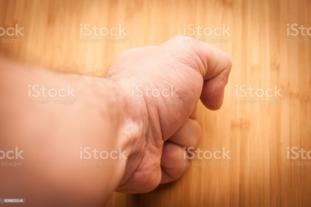 Man's fist hitting a wooden desk stock photo