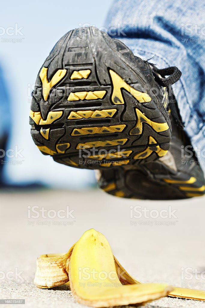 Man's foot approaches dropped banana peel - could be painful! royalty-free stock photo