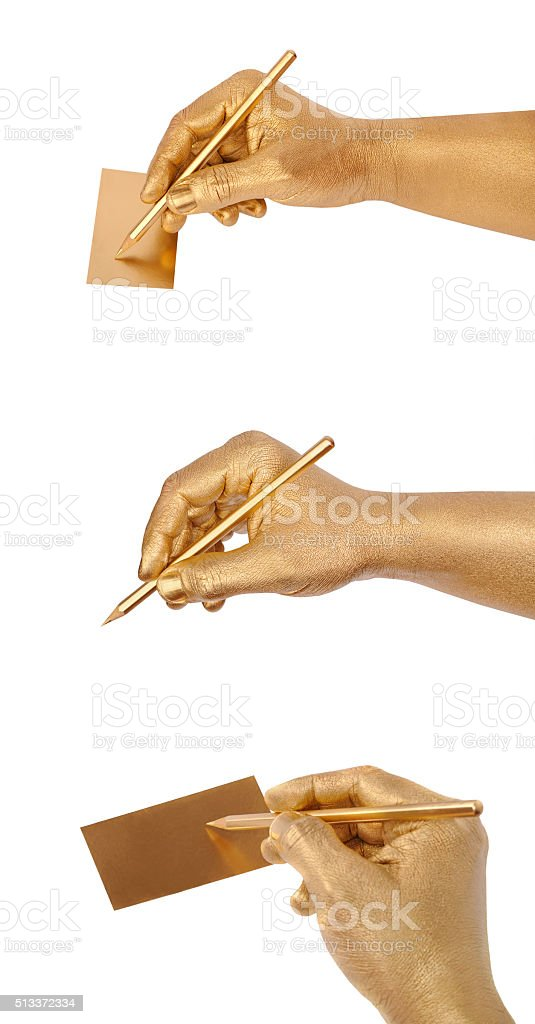Man's golden hand writes on card by a pencil stock photo