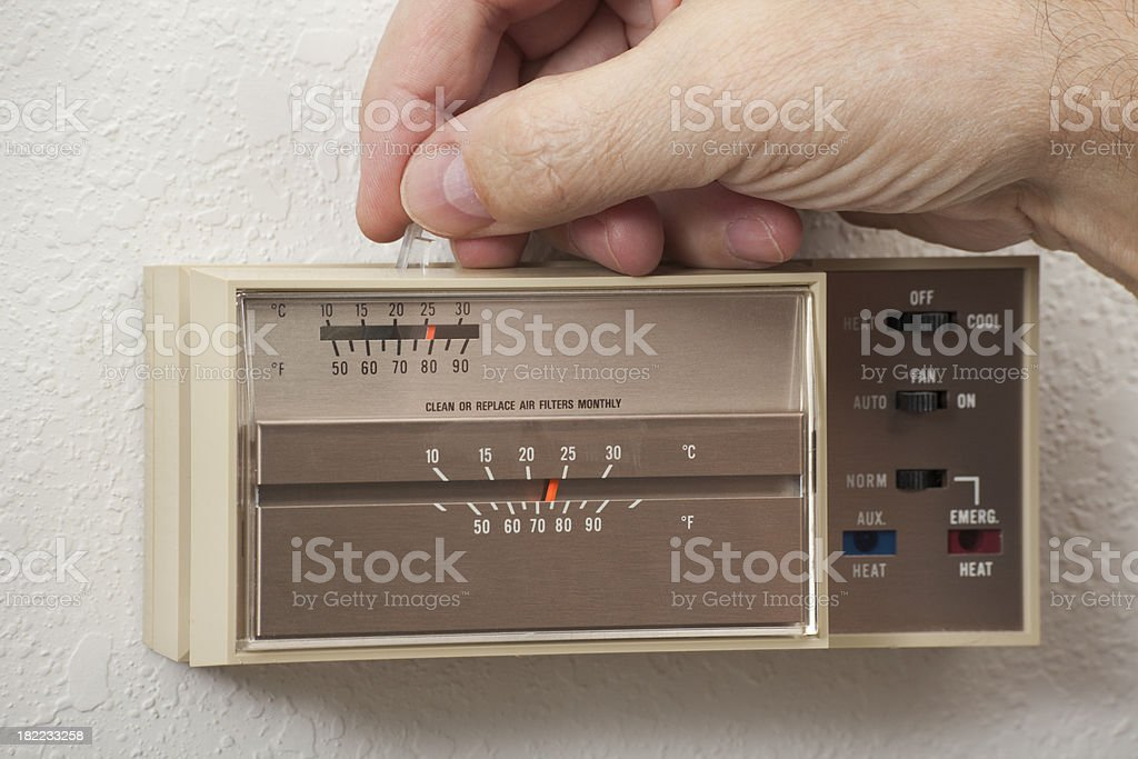 Man's hand adjusting home thermostat stock photo