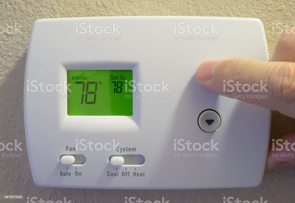 man's hand adjusting home thermostat, summer setting, 78 degrees stock photo