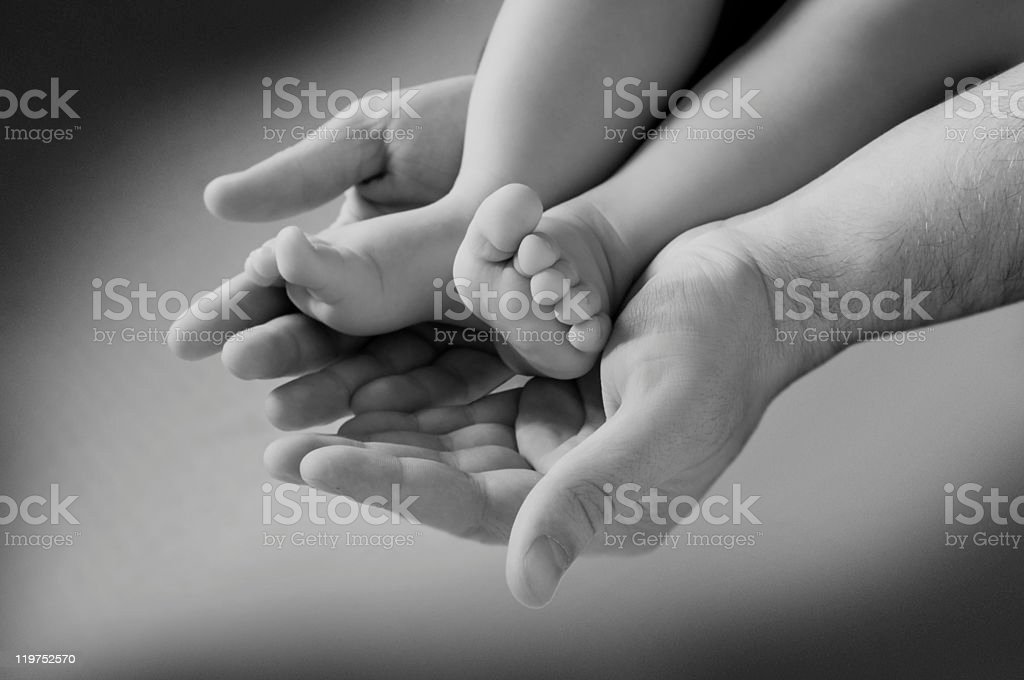 man's hand and children's foot royalty-free stock photo