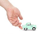 Man's hand assists the cute toy car to drive