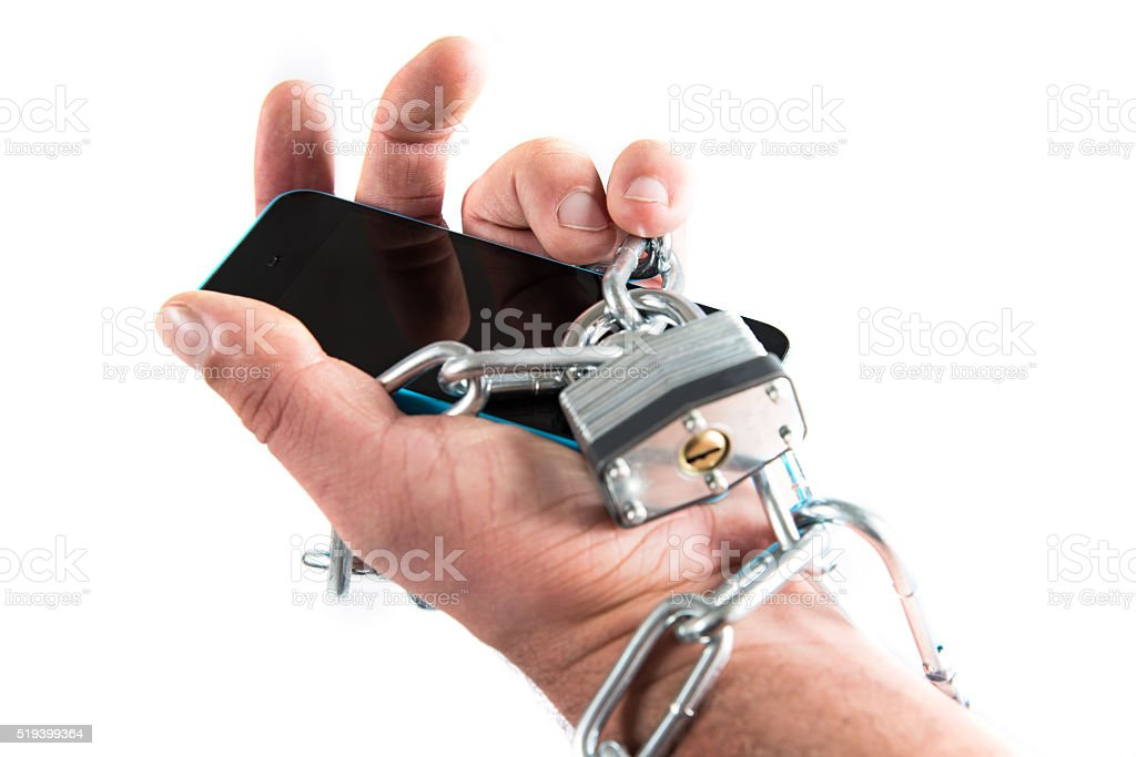Man's Hand Chained to a Cell Phone stock photo