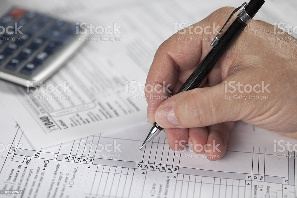 man's hand doing financial 1040 tax work with calculator royalty-free stock photo