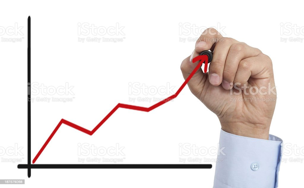 Man's hand drawing graph on clear surface with red slope stock photo