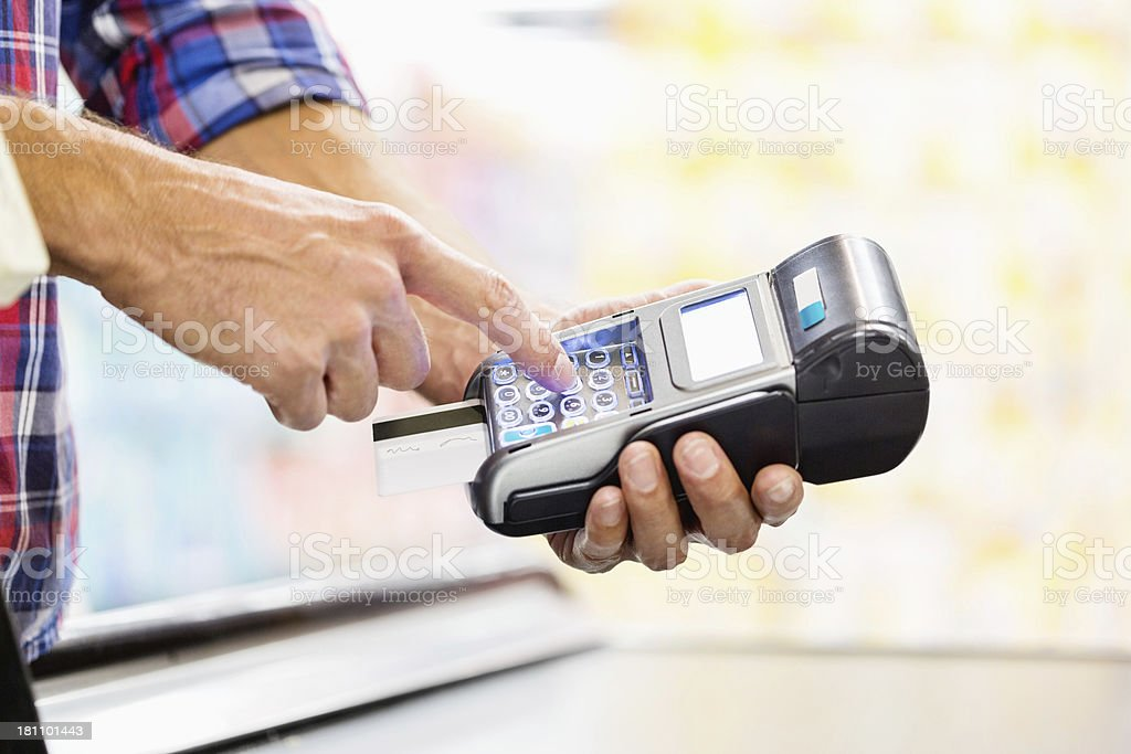 Man's Hand Entering Pin In Credit Card Reader At Counter stock photo
