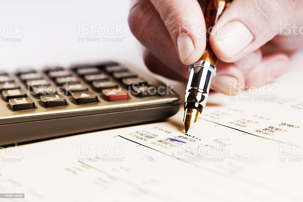 Man's hand erasing figures on documentwith pen, calculator nearby stock photo