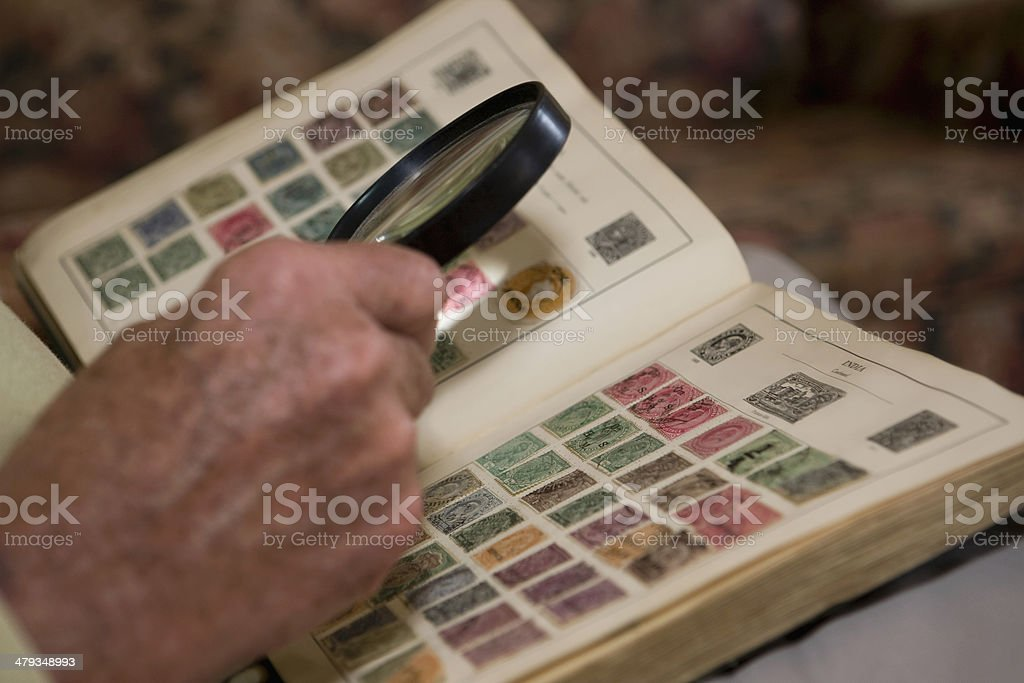 Man's Hand Examining An Old Stamp Book With Magnifying Glass stock photo