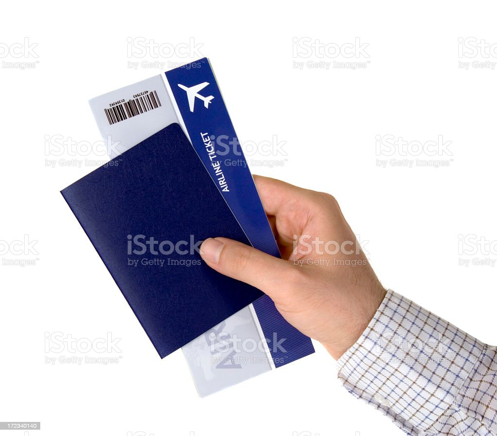 Man's hand holding a blue passport and airplane ticket stock photo