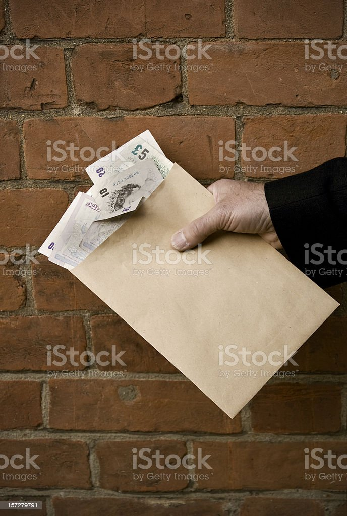 Blackmailer or blackmailed? Man's hand with British banknotes in envelope stock photo