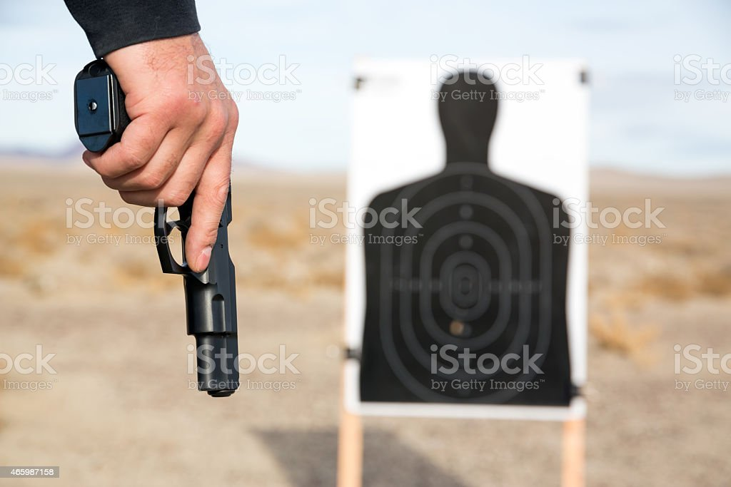 Man's hand holding a gun with a target in the background stock photo