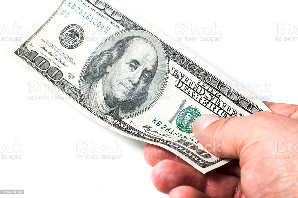 man's hand holding a one hundred dollar bill stock photo