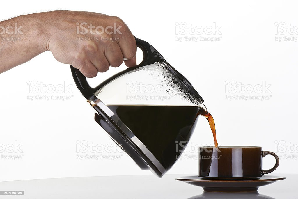 man's hand holding and pouring coffee into a brown cup stock photo
