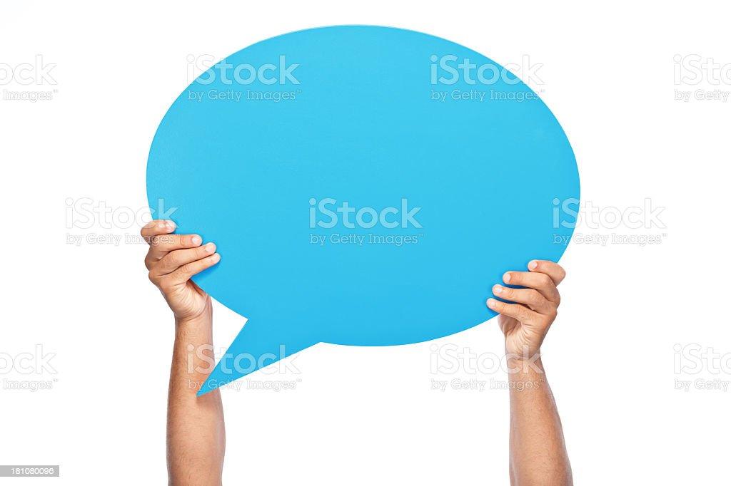 Man's hand holding big blue speech bubble stock photo