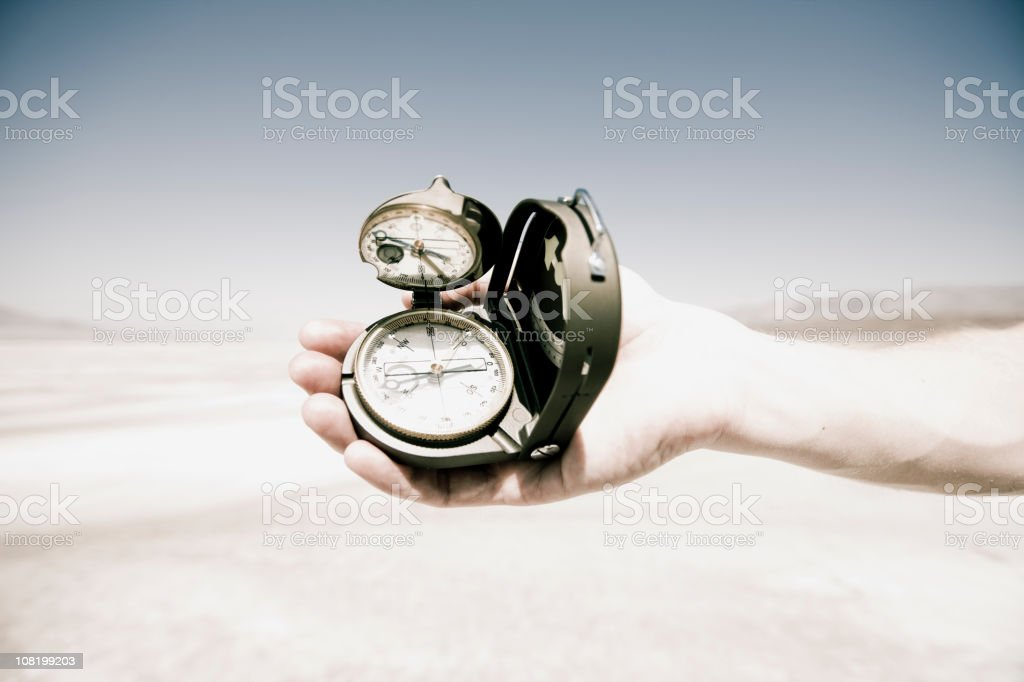 Man's Hand Holding Compass in Middle of Desert royalty-free stock photo