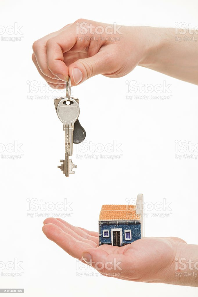 Man's hand holding keys and a toy house stock photo