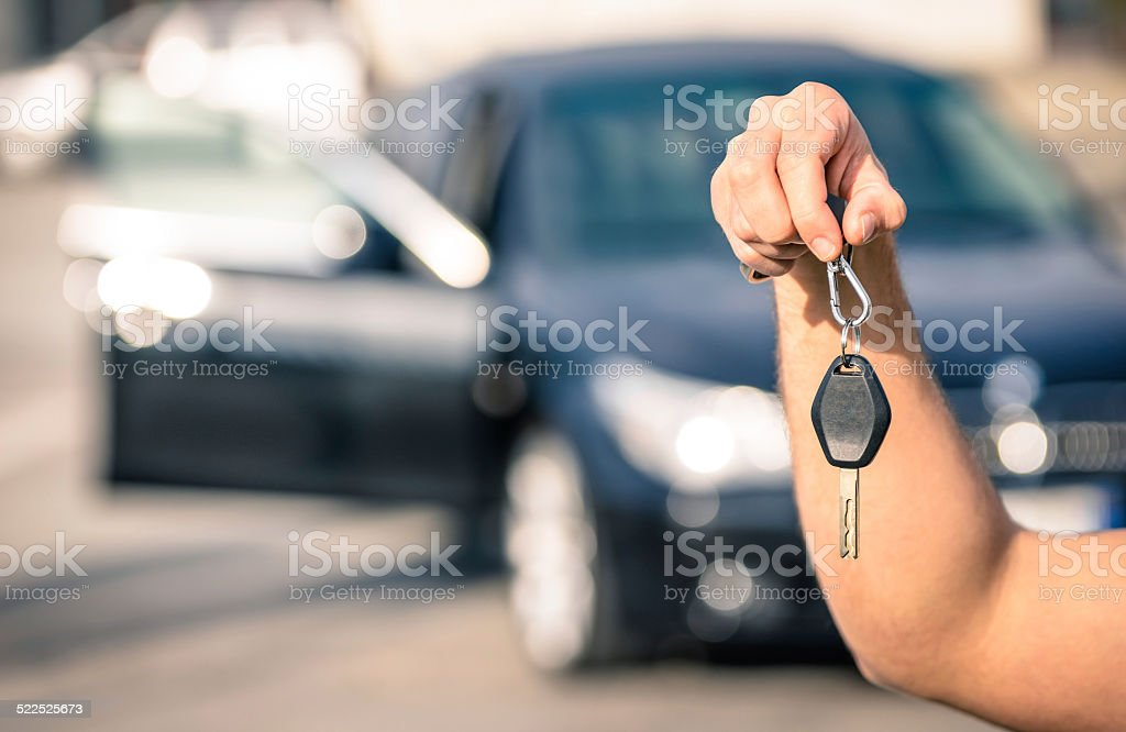 Man's hand holding modern car keys ready for rental stock photo