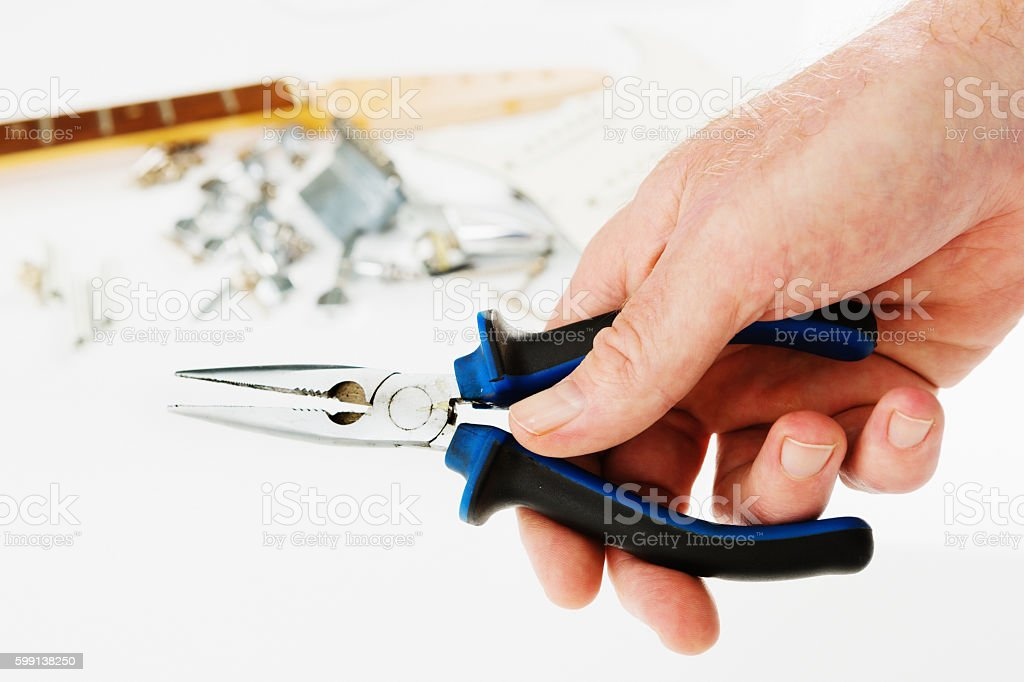 Man's hand holding pliers, ready to fix dismantled electric guitar stock photo