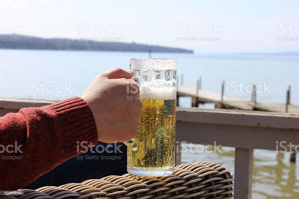 Man's hand holding the beer mug with the lake background. stock photo