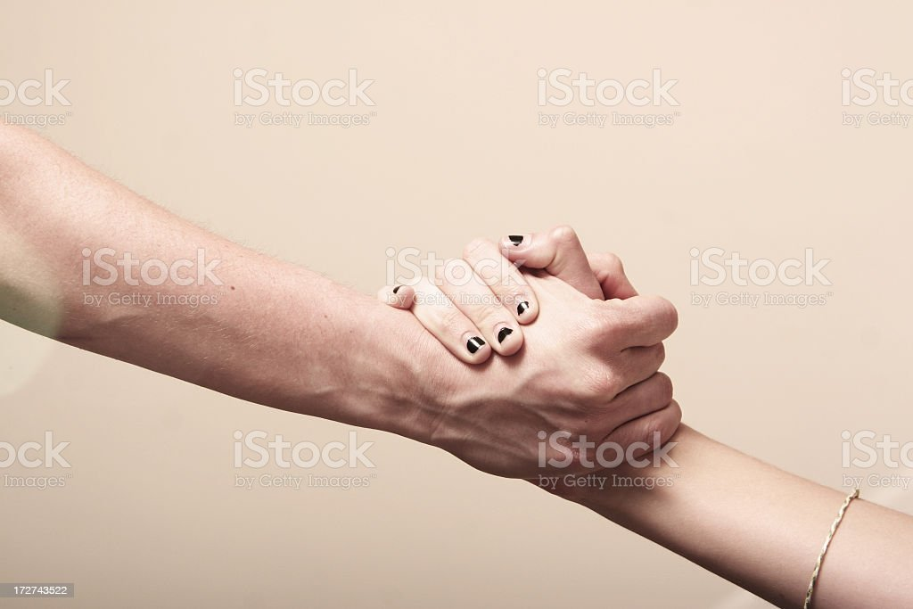 A man's hand holding tight with a woman's hand royalty-free stock photo