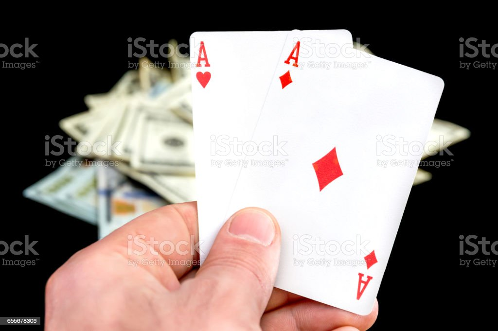 Man's hand holding two aces on dollars background. stock photo