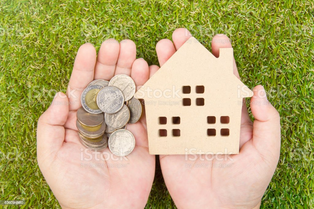 Man's hand holding wooden house toy on ground green grass stock photo