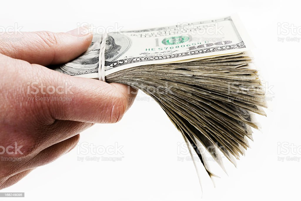 Man's hand holds out bundle of US dollars royalty-free stock photo