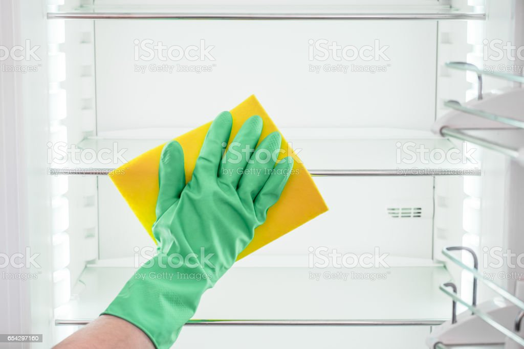 Man's hand in green rubber protective gloves cleaning empty refrigerator stock photo