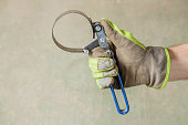 Man's hand in protective glove holding a oil filter wrench.