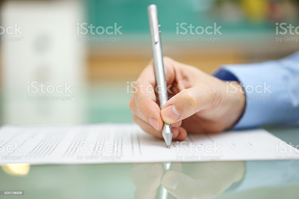 mans hand is  writing document at home on desk stock photo