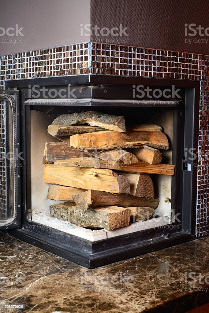 Mans hand load logs in the fireplace stock photo