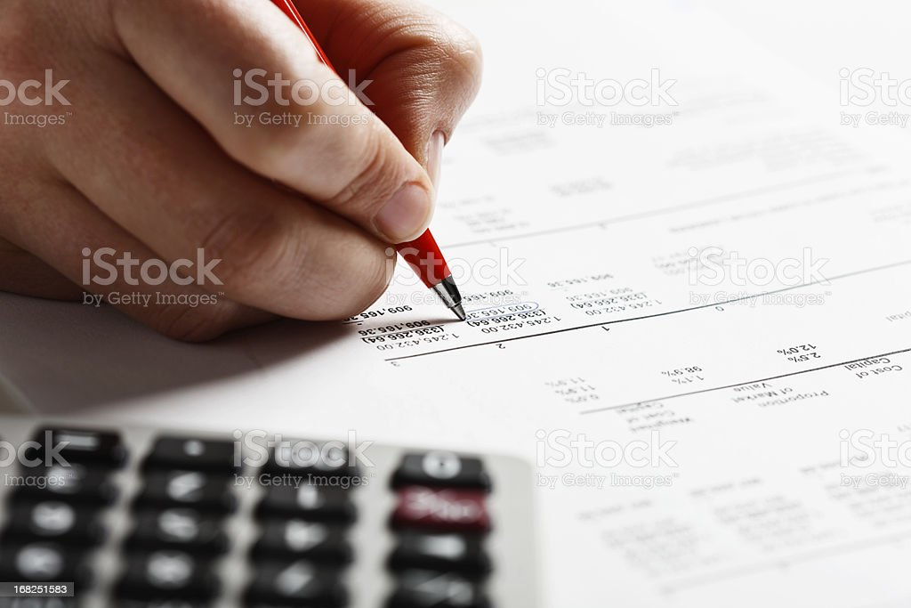 Man's hand marking items on financial document with calculator nearby stock photo