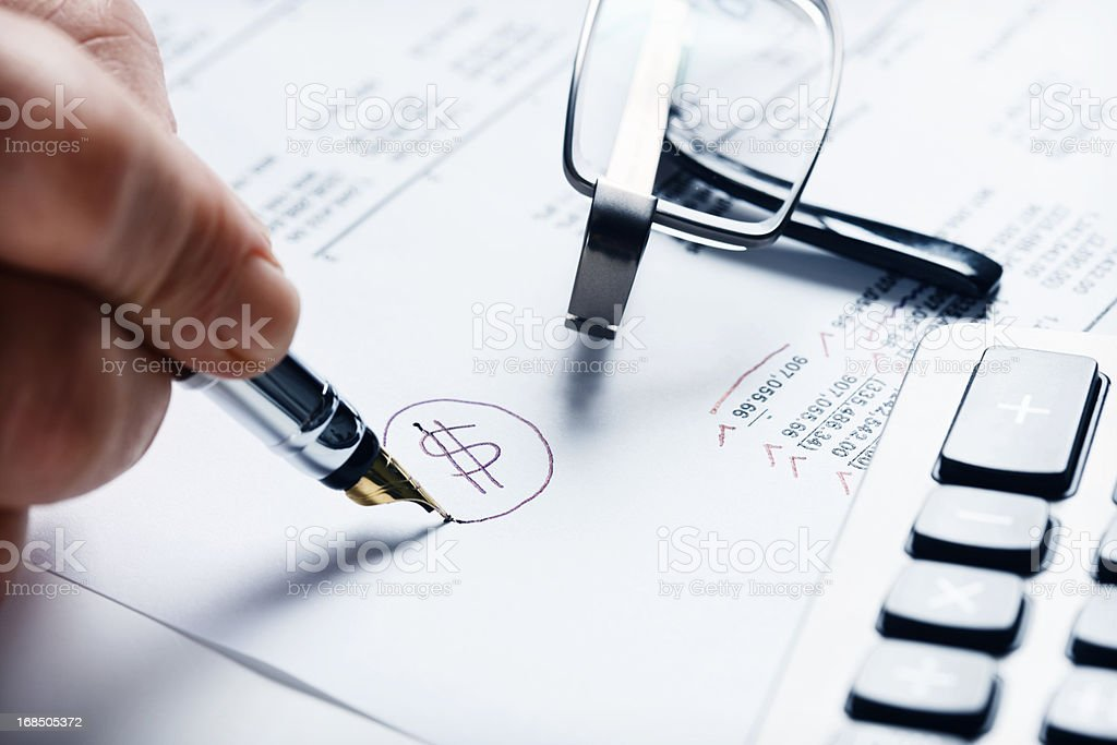 "Man's hand marks ""$"" next to financial spreadsheet royalty-free stock photo"