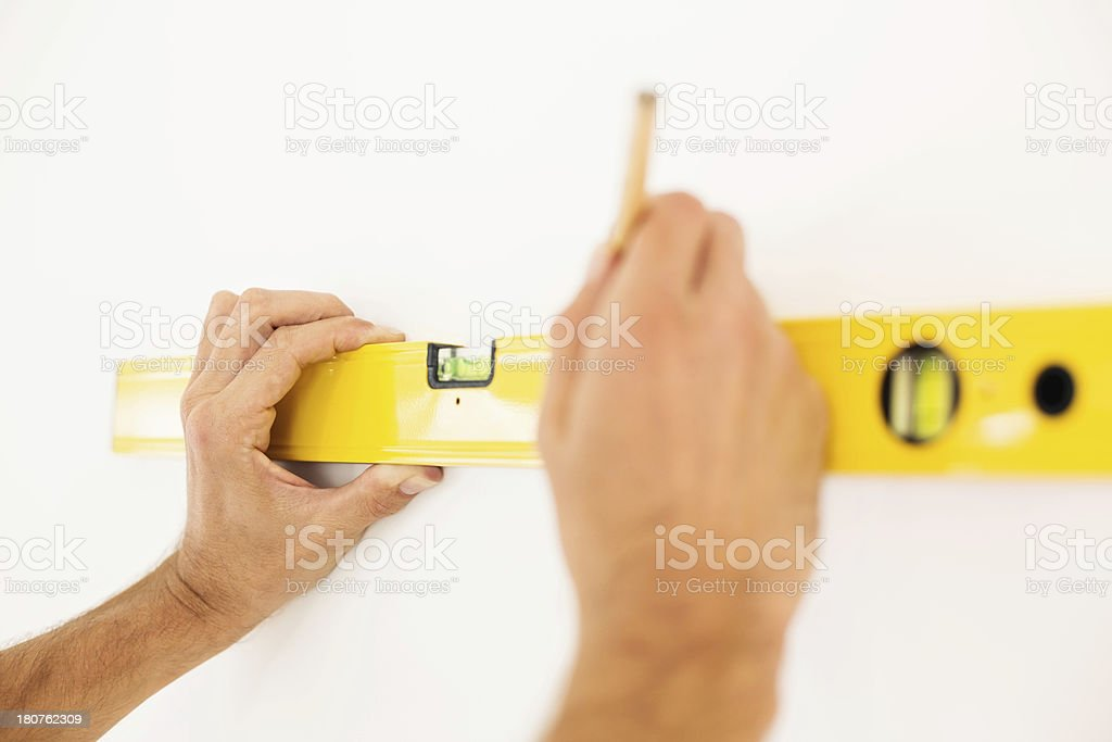 Man's Hand Measuring Wall With Level At Home royalty-free stock photo