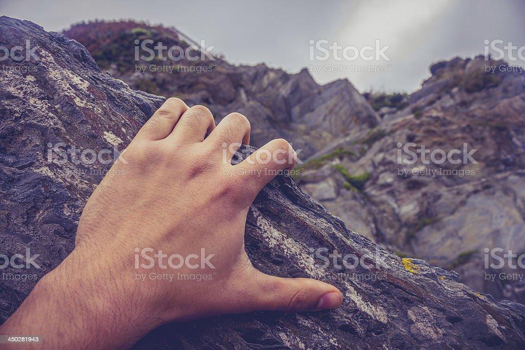 Man's hand on rock stock photo