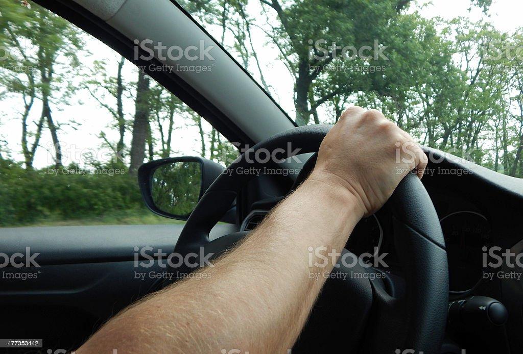 Mans hand on steering wheel stock photo